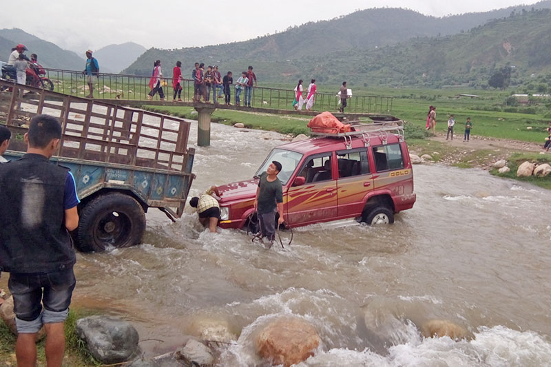 A jeep is seen stuck in the middle of a rivulet along Chinchu-Jajarkot road section in Jajarkot district, on Tuesday, August 15, 2017. Photo: RSS