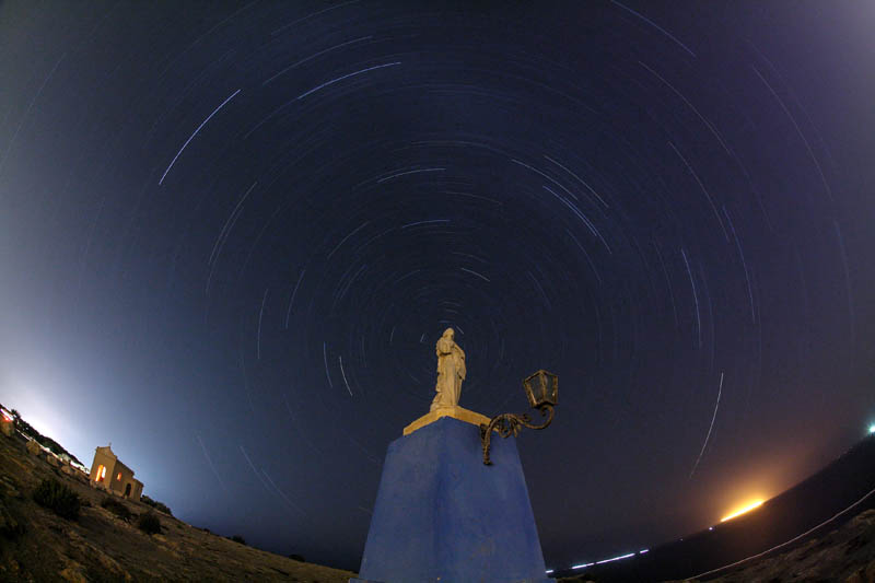 A 90 minute long exposure shows star trails around the Polaris, commonly known as the North Star, hidden behind a statue of the Madonna overlooking the sea at l-Ahrax Point on Marfa Ridge, outside the village of Mellieha, Malta, August 23, 2017.  Photo: Reuters