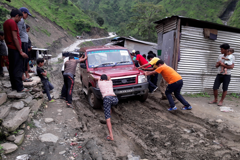 Locals push a jeep stuck in a muddy road at Tipada along the Sanphe-Martadi stretch, in Bajura, on Tuesday, August 1, 2017. Photo: Prakash Singh
