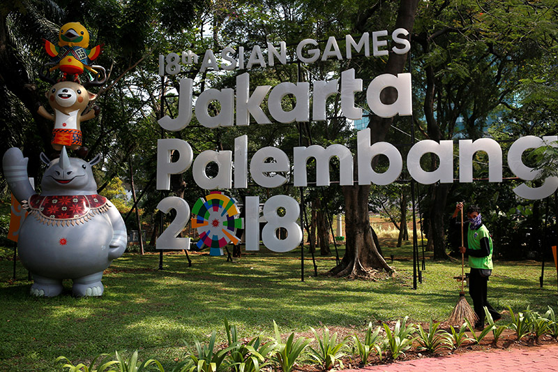 A worker cleans near a sign for the upcoming 2018 Asian Games, which would be held in both Jakarta and Palembang, Sumatra, in Jakarta, Indonesia, on  September 17, 2017. Photo: Reuters