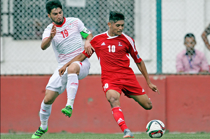 Nepal's striker Bimal Gharti Magar (red) dribbles past Tajikistan player during AFC Asian Cup 2019 Qualifier at ANFA Complex ground, Lalitpur, on Tuesday, September 5, 2017. Photo: THT