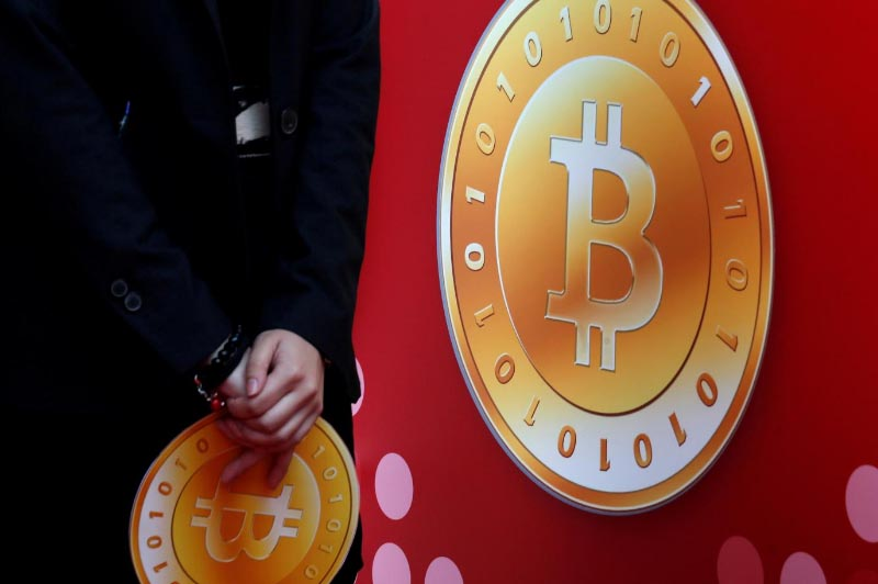 An attendant holds a bitcoin sign during the opening of Hong Kong's first bitcoin retail store, on February 28, 2014. Photo: Reuters