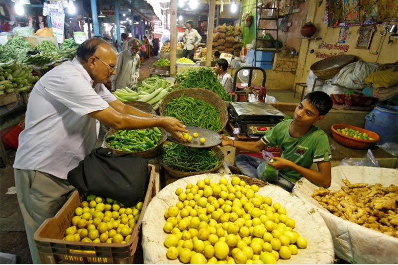 A man buys lemons at a market in Ahmedabad, India, on September 12, 2017. Photo: Reuters