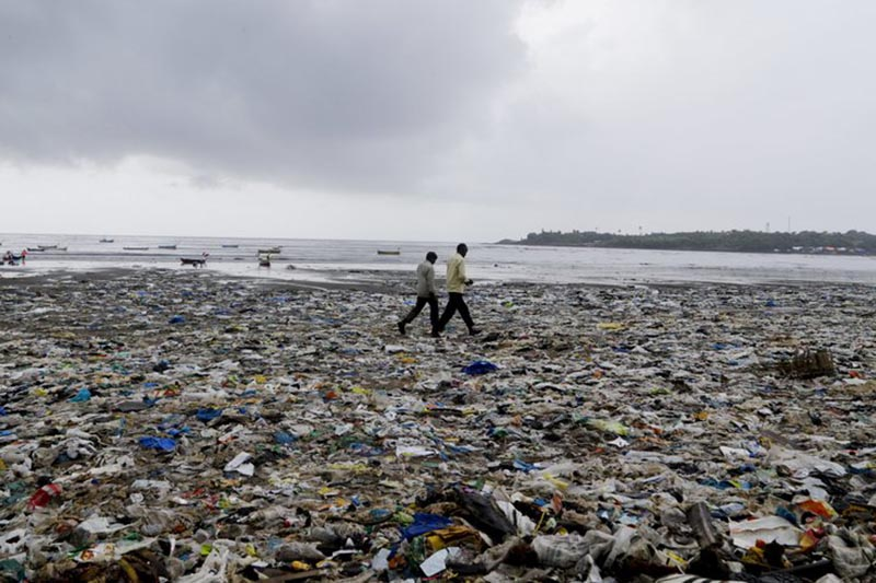 People walk past garbage at the Versova beach on the Arabian Sea coast in Mumbai, India, on August 19, 2017. Photo: AP/ File