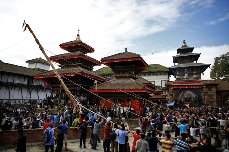 Devotees erecting the Indradhoj Linga, a ceremonial pole commencing the first day of the eight-day long Indrajatra festival, celebrated to honor Indra, the King of Heaven and Lord of Rains in Hanumandhoka, Kathmandu, on Sunday, September 3, 2017. Photo: Skanda Gautam