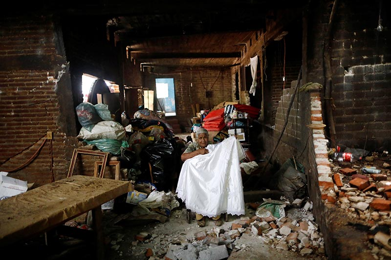 Justina Escamilla (88), who returned to her house to retrieve her belongings, poses for a photo with her wedding dress inside her destroyed house after an earthquake in San Juan Pilcaya, at the epicenter zone, Mexico, on September 25, 2017. Photo: Reuters