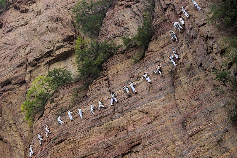People move up a rope running along a rock face in the Qingyao mountains outside Luoyang, Henan province, China, on September 23, 2017. Photo: Reuters