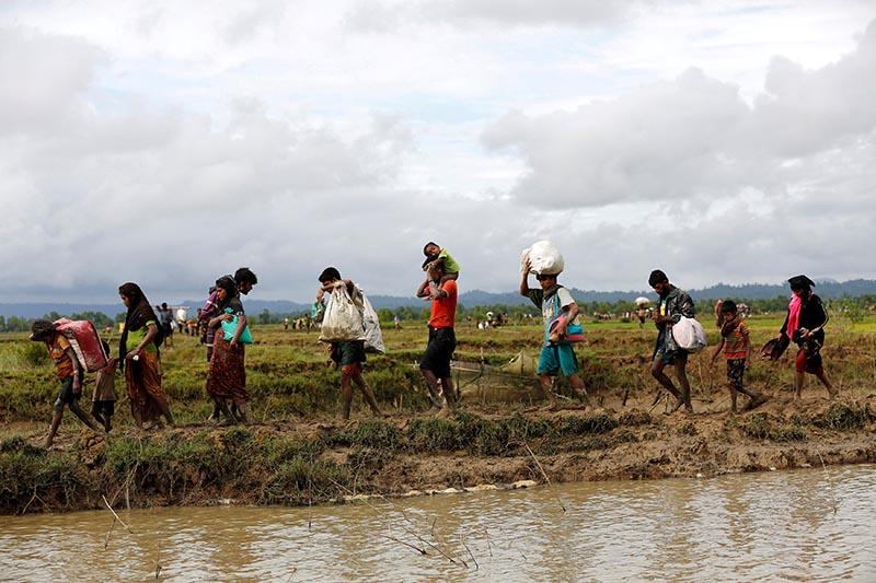 A group of Rohingya refugee people walk towards Bangladesh after crossing the Bangladesh-Myanmar border in Teknaf, Bangladesh, on September 1, 2017. Photo: Reuters