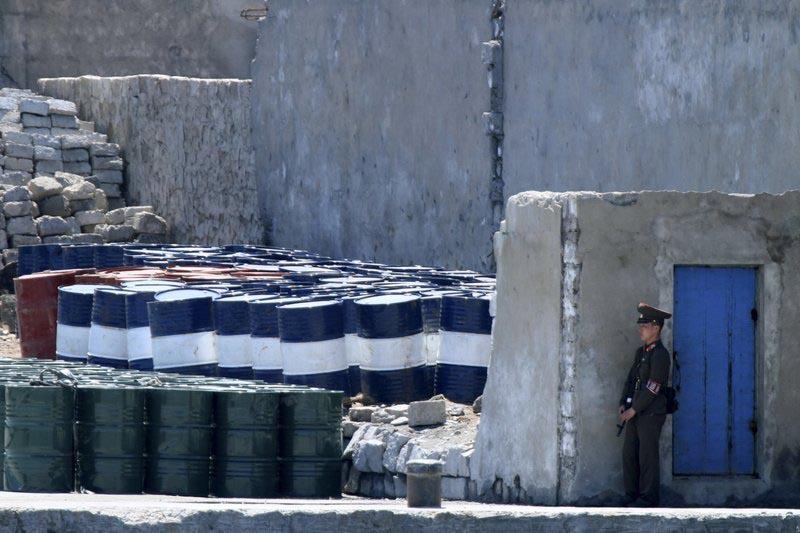 A North Korean solder stands guard near barrels stacked up near the river bank of the North Korean town of Sinuiju, opposite the Chinese border city of Dandong, on  May 8, 2016. Photo: Chinatopix via AP/ File
