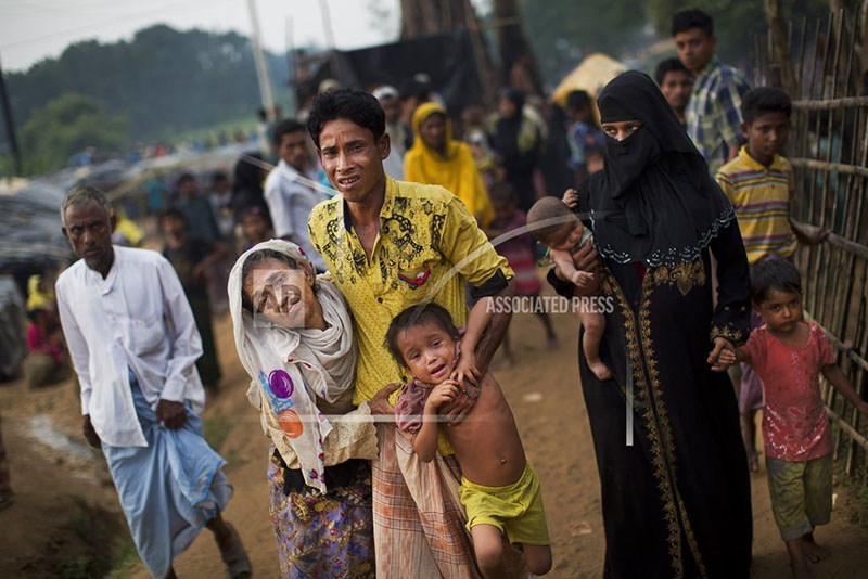 An exhausted Rohingya helps an elderly family member and a child as they arrive at Kutupalong refugee camp after crossing from Myanmmar to the Bangladesh side of the border, in Ukhia, Tuesday, Sept. 5, 2017. Photo: AP