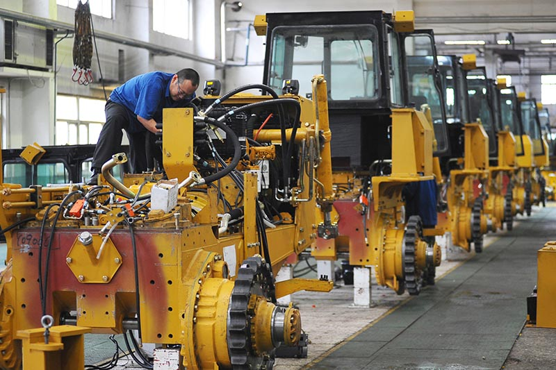 An employee works at an assembly line of bulldozers at a factory in Zhangjiakou, Hebei province, China, on  October 13, 2017. Photo: Stringer via Reuters