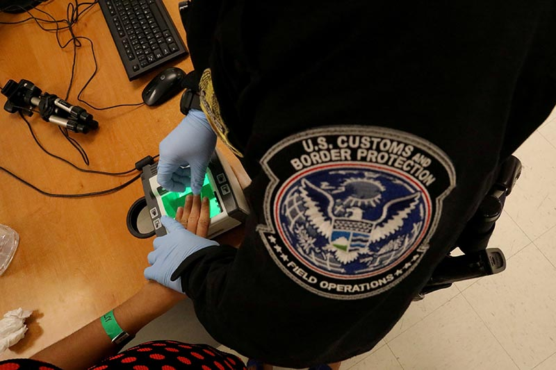A woman who is seeking asylum has her fingerprints taken by a US Customs and Border patrol officer at a pedestrian port of entry from Mexico to the United States, in McAllen, Texas, US, on May 10, 2017. Photo: Reuters