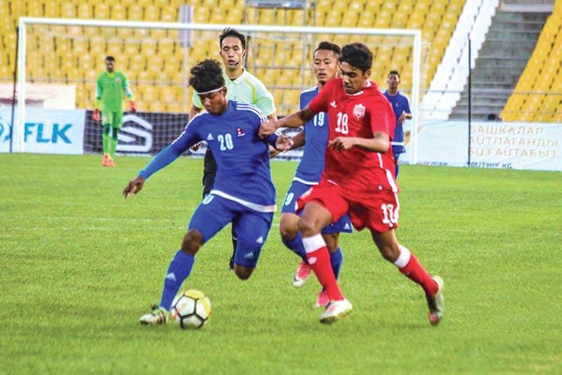 Nepalu2019s Bikash Khawas and Bahrainu2019s Ahmed Abdulrahman Alsherooqi (right) vie for the ball during their AFC U-19 Championship Qualifiers match in Bishkek on Thursday.