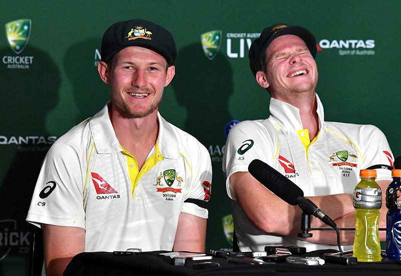 Australia's captain Steve Smith reacts as team mate Cameron Bancroft speaks during a media conference after the first Ashes test match at the Gabba ground in Brisbane, Australia, on November 27, 2017. Photo:  AAP/Darren England via Reuters