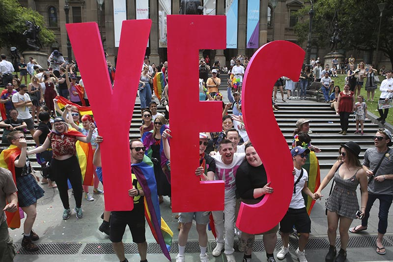People celebrate after the announcement of the same-sex marriage postal survey result in front of the State Library of Victoria in Melbourne, Australia, on Wednesday, November 15, 2017. Photo: David Crosling/AAP Image via AP