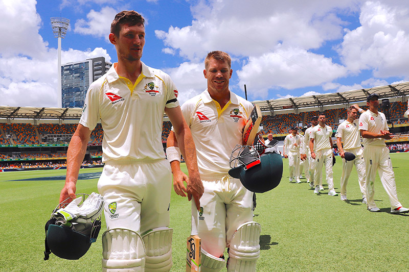 Australia's Cameron Bancroft walks off the field with team mate David Warner and England team players after hitting the winning runs to win the first Ashes cricket test match. Photo: Reuters