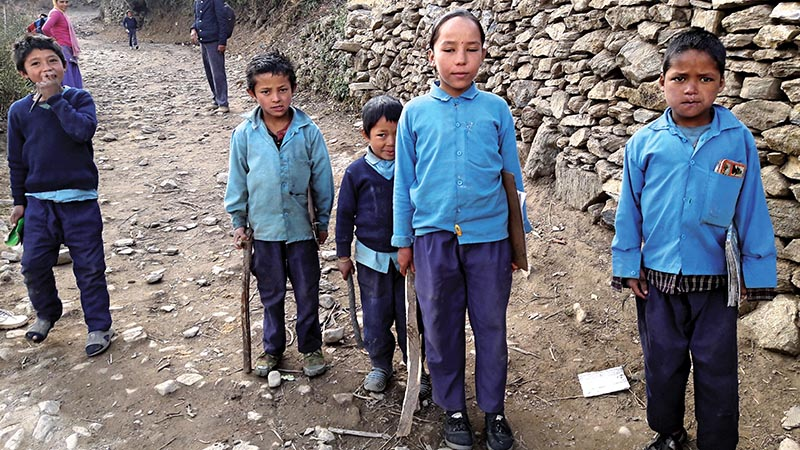 Students carrying firewood to school to prepare nutritional supplement, in Bajura, on Monday. Photo: THT