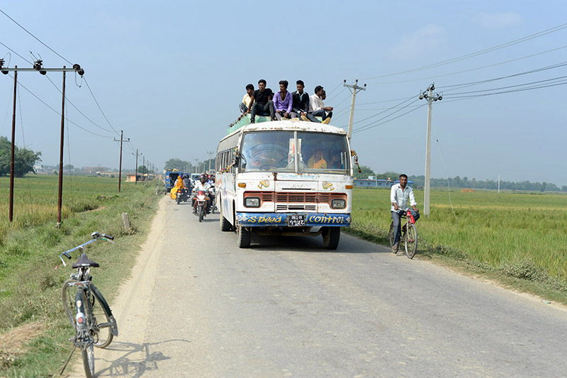 Passengers sit on a bus hood as they travel along a rural road in Parsa district, on Thursday, November 09, 2017. Photo: RSS