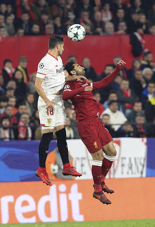 Liverpool's Mohamed Salah jumps for the ball with Sevilla's Sergio Escudero (left), during a Champions League group E soccer match between Sevilla and Liverpool, at the Ramon Sanchez Pizjuan stadium in Seville, Spain, on Tuesday, November 21, 2017. Photo: AP