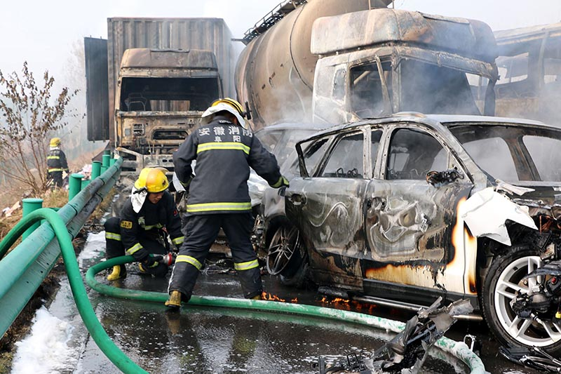 Firefighters work to put out fires in vehicles after a highway accident in Fuyang in central China's Anhui province, on Wednesday, November 15, 2017. Photo: Chinatopix via AP