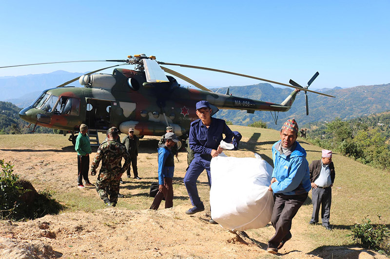 Temporary police with the help of office assistant carry election materials for upcoming elections  transported through helicopter in Khotang district, on Thursday, November 09, 2017. Photo: RSS