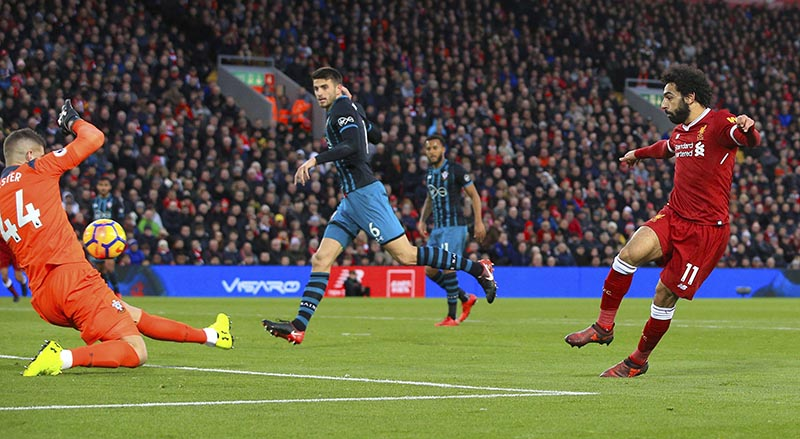 Liverpool's Mohamed Salah, right, scores his side's second goal of the game during the English Premier League soccer match Liverpool versus Southampton at Anfield, Liverpool, England, Saturday Nov. 18, 2017. (Peter Byrne/PA via AP)