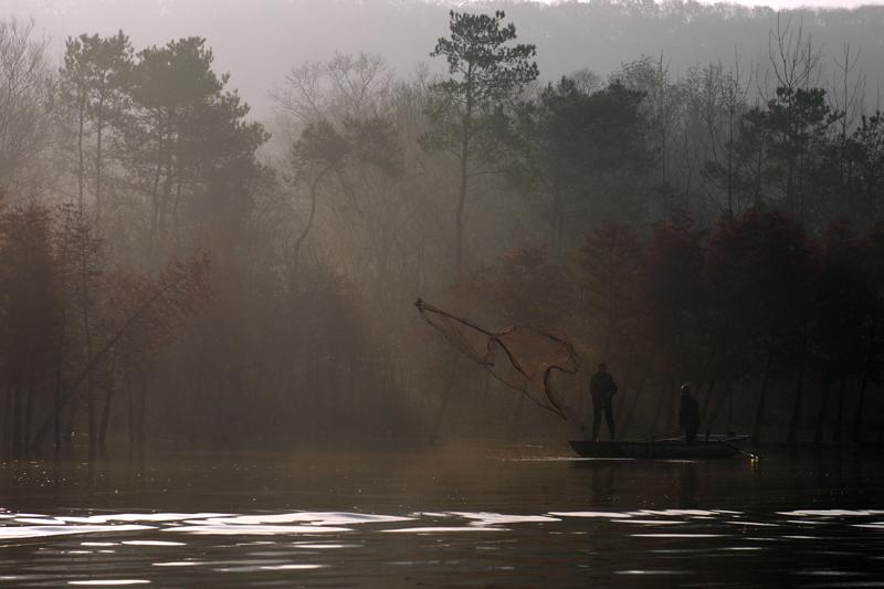 Fishermen cast their fishing net into a lake on a foggy day in Huai'an, Jiangsu province, China November 28, 2017. Photo: REUTERS/Stringer