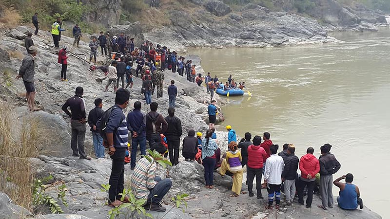 People observe the incident site while the security personnel row a rafting boat in search of the bus accident victims in Trishuli River at Fisling, in Ichchhakamana Rural Municipality-3 of Chitwan district, on Wednesday, November 29, 2017. A bus heading to Arghakhanchi from Kathmandu plunged about 100 metres into the river. Photo: Tilak Ram Rimal/THT
