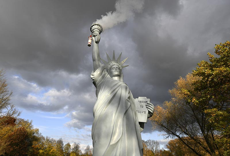A replica of the Statue of Liberty by Danish artist Jens Galschiot emits smoke in a park outside the 23rd UN Conference of the Parties (COP) climate talks in Bonn, Germany, on Friday, November 17, 2017. Photo: AP