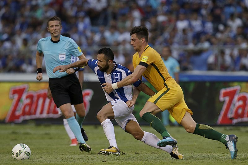 Australia's Tomi Juric (right) fights for the ball with Honduras' Alfredo Mejia, center, as referee Daniele Orsato, from Italy, looks on, during the first leg of a soccer World Cup qualifier play-off at the Olympic Stadium in San Pedro Sula, Honduras, on Friday, November 10, 2017. Photo: AP
