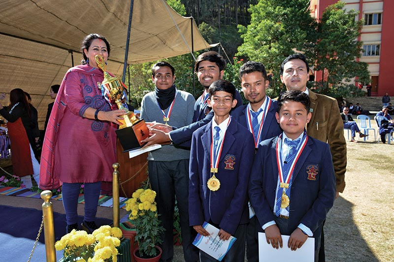 Headmistress of Modern Indian School Maya Rana handing over the trophy to MIS table tennis team members after the Inter-school Tournament in Kathmandu on Sunday. Photo: THT