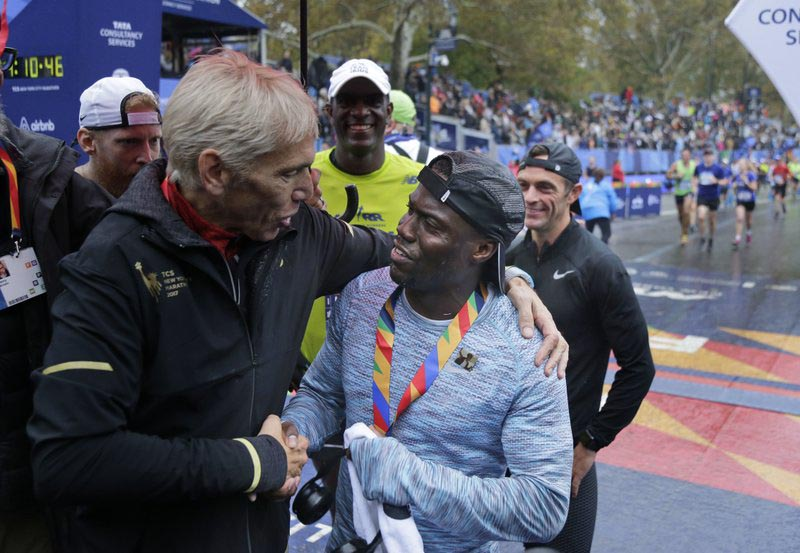 Marathon race director Peter Ciaccia, left, greets comedian Kevin Hart as he crosses the finish line of the New York City Marathon in New York, on Sunday, November 5, 2017. Photo: AP