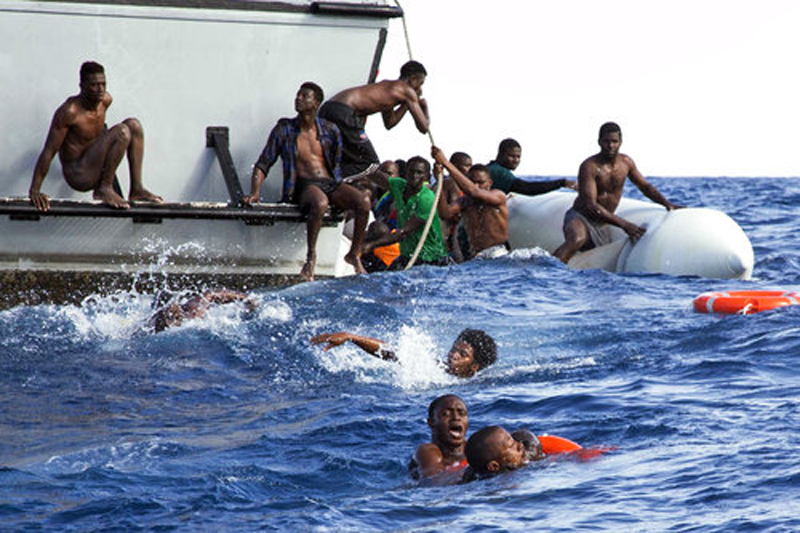 Migrants from a sinking inflatable dinghy try to get on a Libyan coast guard boat during a rescue operation at sea, on Monday, November 6, 2017. Photo: AP