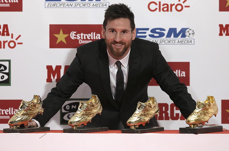 FC Barcelona's Lionel Messi poses with his his fourth Golden Shoe award after receiving his fourth Golden Shoe award for leading all of Europe's leagues in scoring last season in Barcelona, Spain, on Friday, November 24, 2017. Photo: AP