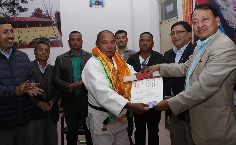 NSC Member Secretary Keshab Kumar Bista handing over the sixth DAN certificate and belt to judoka Khadak Bahadur Dahal, in Kathmandu, in November, 2017. Photo: THT