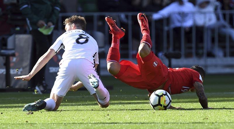 New Zealand's Michael McGlinchey (left), tackles Peru's Yoshimar Yotun during their Soccer World Cup qualifying match in Wellington, New Zealand, on Saturday, November 11, 2017. Photo: Ross Setford/SNPA via AP