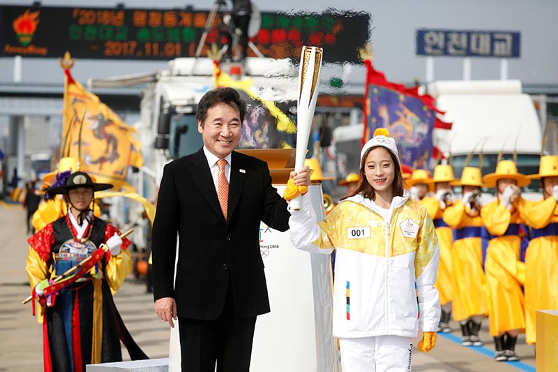 South Korean Prime Minister Lee Nak-yeon attends the Olympic torch relay ceremony with figure skating prospect and the first torchbearer of the country You Young on the Incheon bridge in Incheon, South Korea, on November 1, 2017. Photo: Reuters