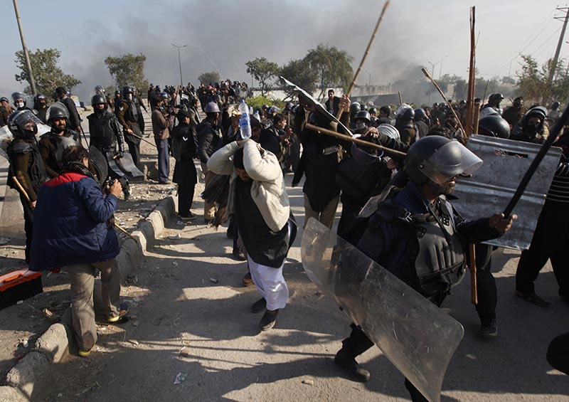 Police officers beat a protester during a clash in Islamabad, Pakistan, on Saturday, November 25, 2017. Photo: AP