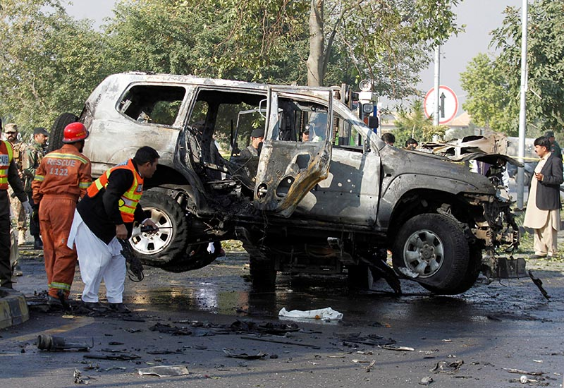 Rescue personnel inspect a vehicle damaged by a suicide bomber which killed a senior Pakistani police official on his way to work in Peshawar, Pakistan, on November 24, 2017. Photo: Reuters