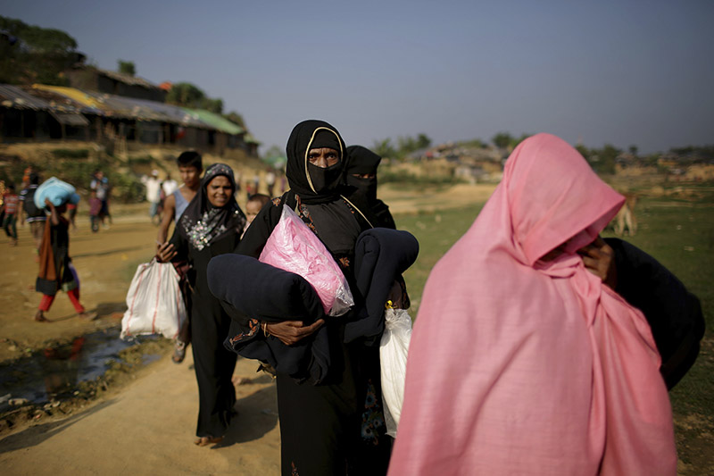 FILE - In this Tuesday, Nov. 21, 2017, file photo, Rohingya Muslim women carry blankets and other supplies they collected from aid distribution centers in Kutupalong refugee camp in Bangladesh. Photo: AP
