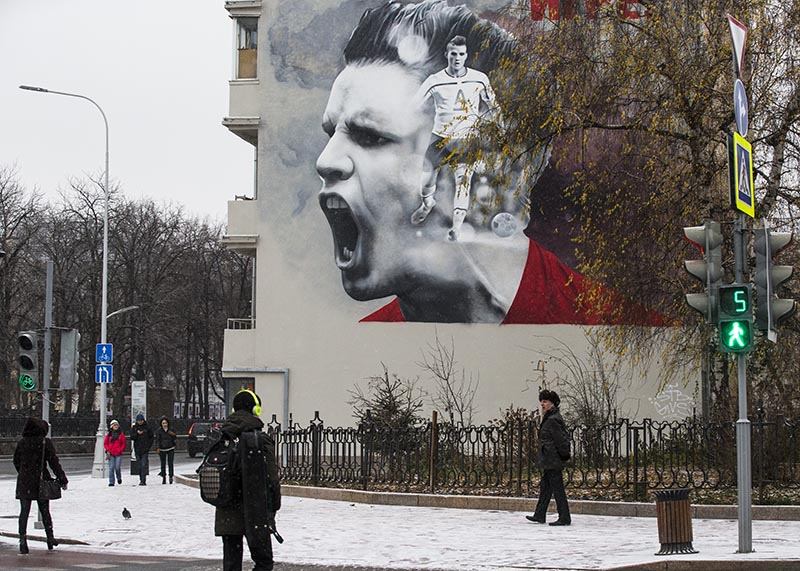 People walk past a huge poster promoting the upcoming soccer World Cup 2018 tournament in Moscow, Russia, on Tuesday, November 28, 2017. Photo: AP
