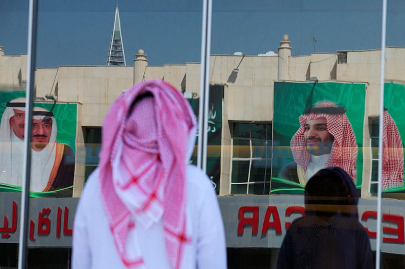 Pictures of Saudi Arabia's King Salman bin Abdulaziz Al Saud and Crown Prince Mohammed bin Salman are reflected in a window as people arrive at a company in Riyadh, Saudi Arabia, November 9, 2017. Photo: Reuters