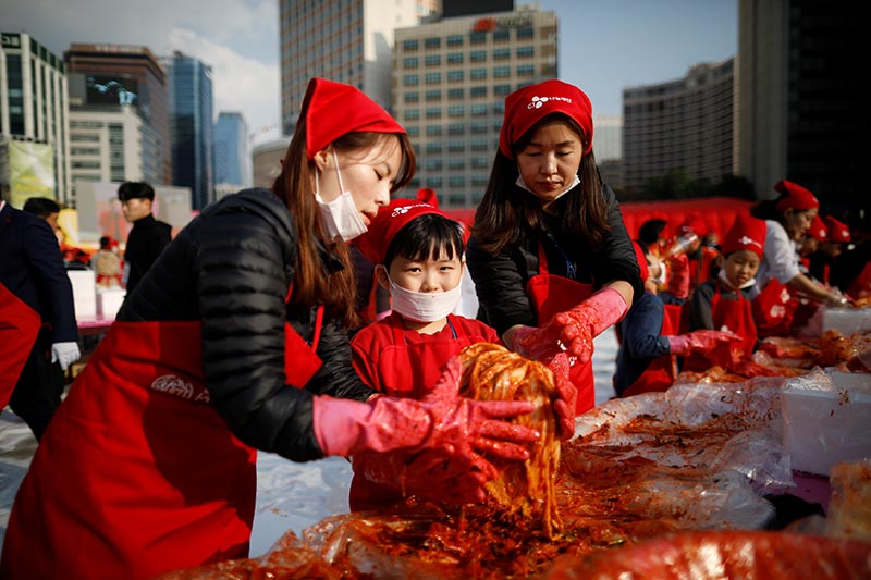 A boy makes traditional Korean side dish kimchi, or fermented cabbage, as he takes part in the Seoul Kimchi Festival in central Seoul, South Korea,on  November 3, 2017. Photo: Reuters