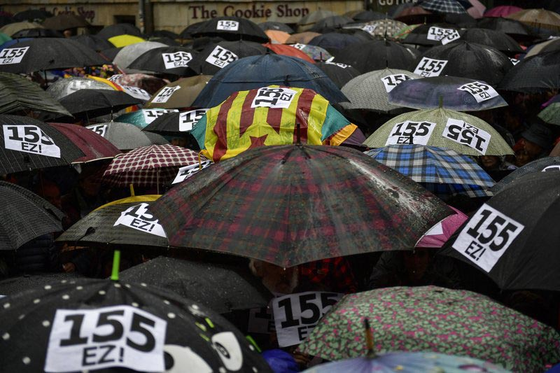 People shelter under umbrellas, at Plaza Consistorial square during a protest against Article 155 of the Constitution, which gives the central government extra powers to re-establish the rule of law in a region, in Pamplona, northern Spain, Spain, on Sunday, November 5, 2017. Photo: AP