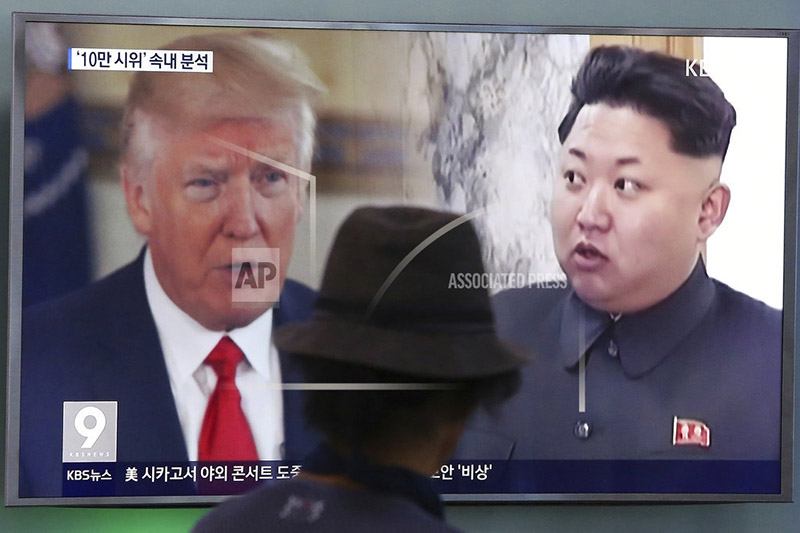 FILE - In this Aug. 10, 2017, file photo, a man watches a television screen showing US President Donald Trump and North Korean leader Kim Jong Un during a news program at the Seoul Train Station in Seoul, South Korea. Photo: AP