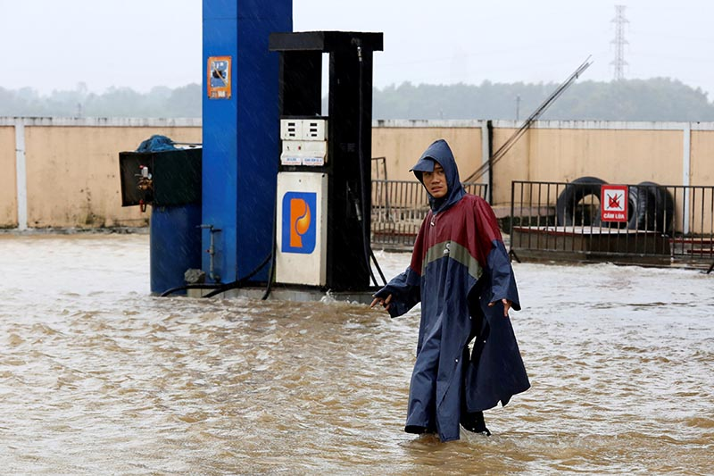 A man walks along a flooded petrol station after typhoon Damrey hits Vietnam in Hue city, Vietnam, on November 5, 2017. Photo: Reuters