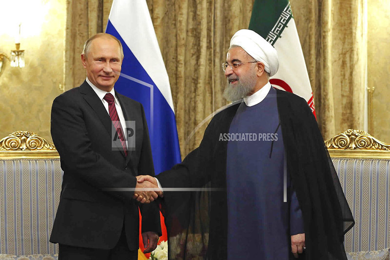 In this photo released by an official website of the office of the Iranian Presidency, Iran's President Hassan Rouhani, right, shakes hands with Russian President Vladimir Putin during their meeting at the Saadabad Palace in Tehran, Iran, Wednesday, Nov. 1, 2017. Photo: AP