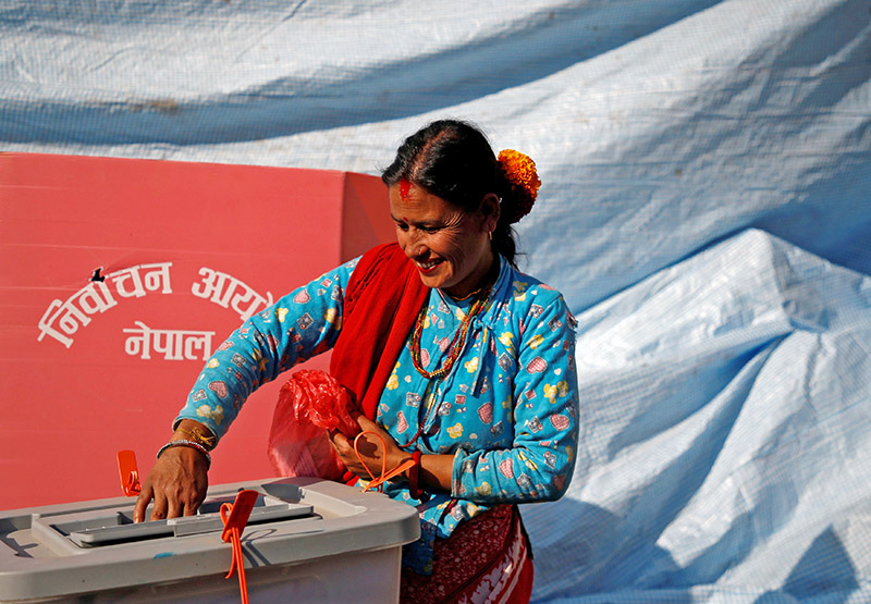 A woman smiles as she cast her vote on a ballot box during the parliamentary and provincial elections in Sindhupalchok District, Nepal November 26, 2017. Photo: Reuters