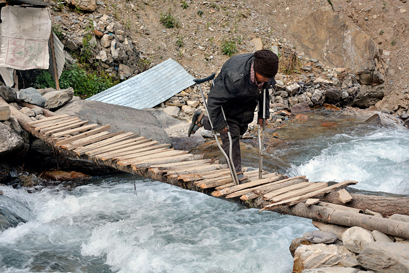 A differently abled person crossess a makeshift wodden bridge over Taman Khola in Baglung district, on Thursday, November 09, 2017. Photo: RSS