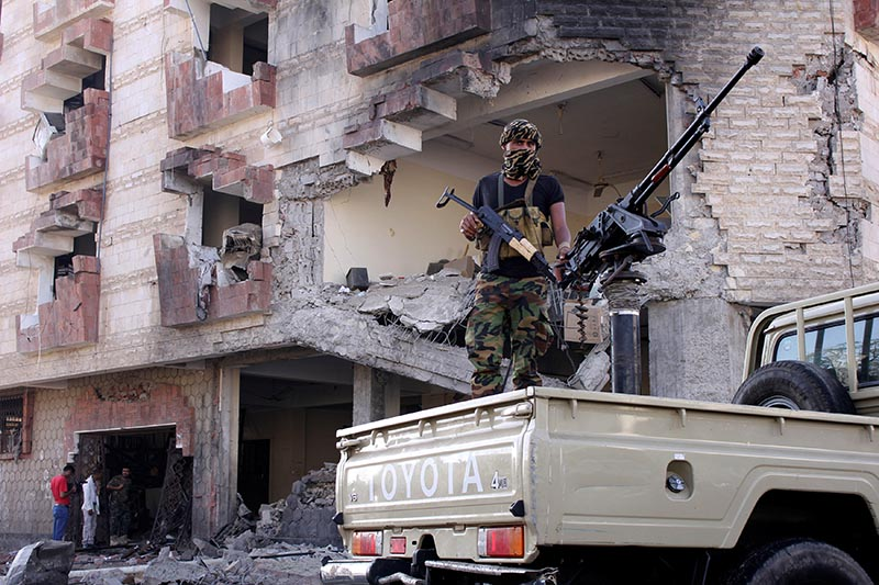 A police trooper mans a machine gun mounted on a patrol truck at the site of a car bomb attack outside the Finance Ministry offices in the southern port city of Aden, Yemen, on  November 29, 2017. Photo: Reuters